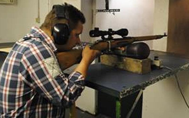Image of a man sitting wearing ear protection holding and aiming a gun on a table