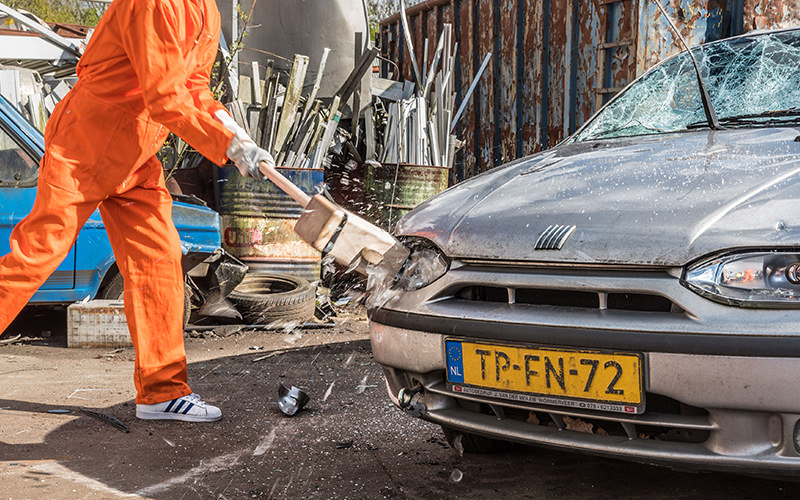 A man smashing a large hammer into the front of a car