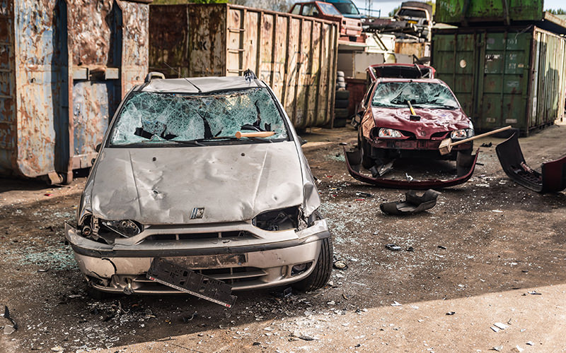 Two cars that have been smashed by weapons