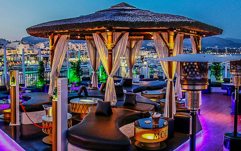 The rooftop terrace of Pangea, featuring a canopy with plush leather seats and curtains