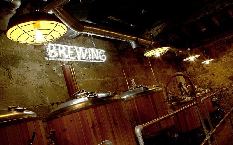 Some big beer vats with Brewing written in neon lighting above