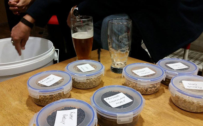 All of the ingredients for beer laid out in Tupperware on a wooden table