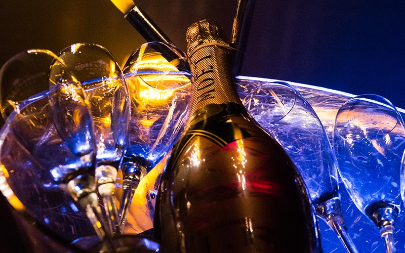A close up of a bottle of Moet in an ice bucket