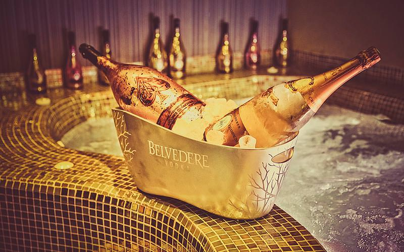 Two bottles of champagne in an ice bucket, with a Jacuzzi in the background