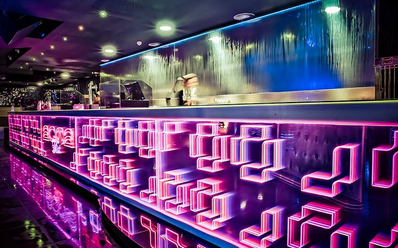 A blurry image of a bartender walking behind the bar, lit-up with pink lights