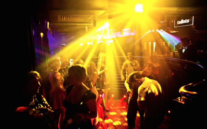 A group of people dancing under strobe lights