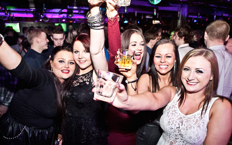 A group of women holding drinks in the air while laughing