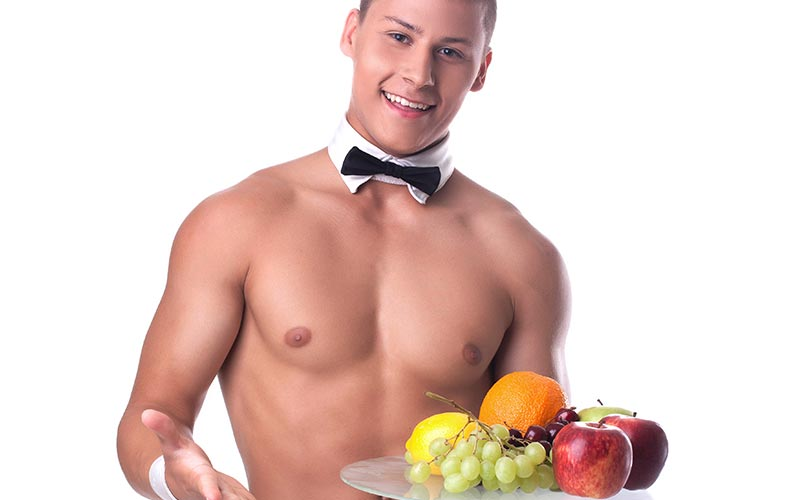 A topless waiter holding a plate of fruit