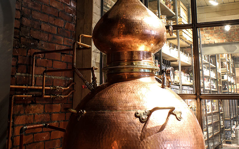 A large copper gin vat