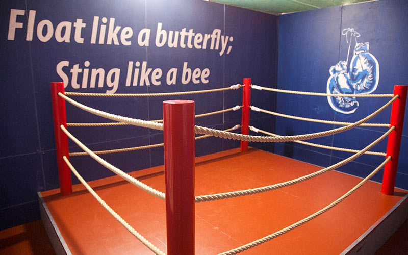 A small boxing ring with a Mohammed Ali saying on the wall behind it