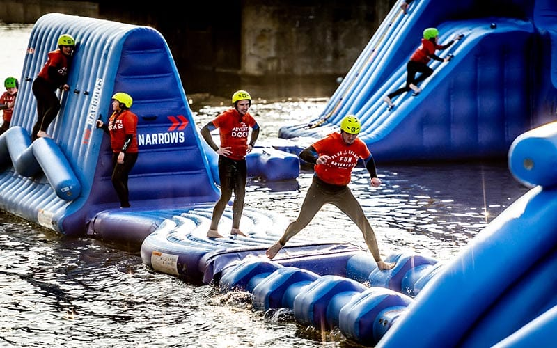 A group of people running across an obstacle course