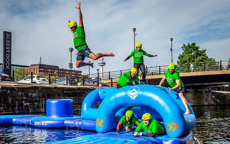 A group of people jumping off an inflatable slide