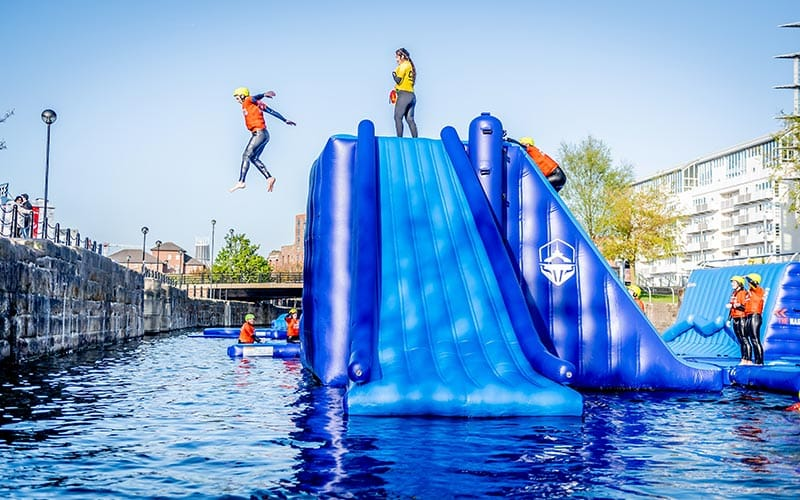 A person jumping off an obstacle into the water