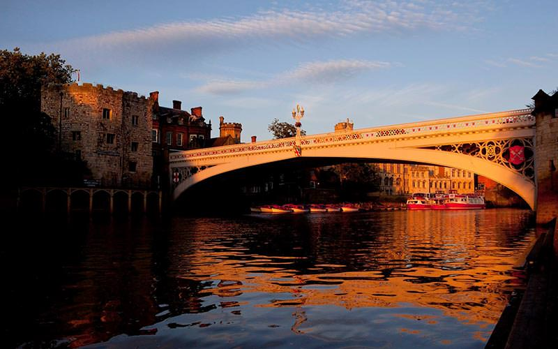 Image of a bridge in york showing the river cruise boats docked in the sunset