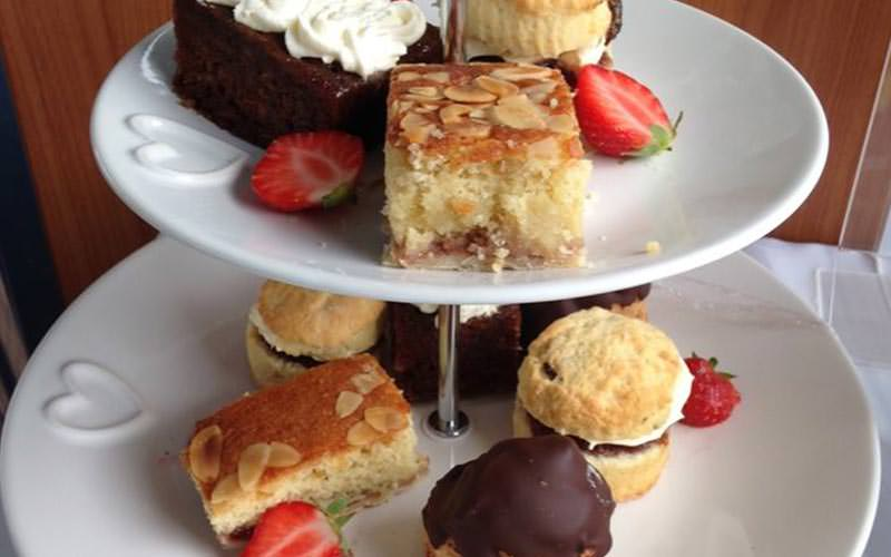 Image of a two tiered cake stand with cakes and scones and sliced strawberries