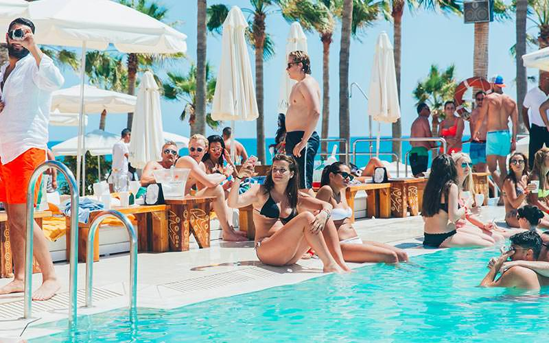 People sat around the pool and on sunbeds at Nikki Beach