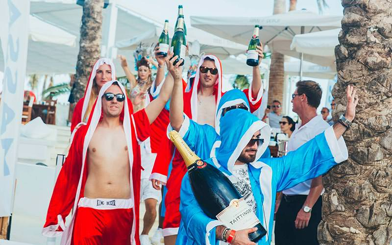 Men holding champagne bottles in the air whilst dressed as boxers