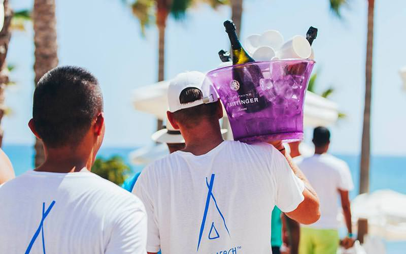 A man carrying a purple ice bucket, filled with cups and champagne, on his shoulder with another man walking behind him