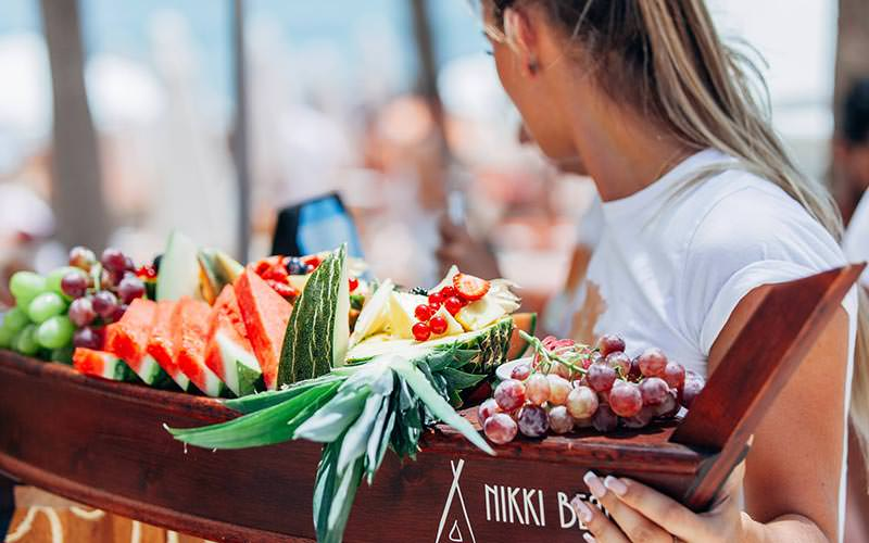 A woman carrying fruit in a boat-shaped tray