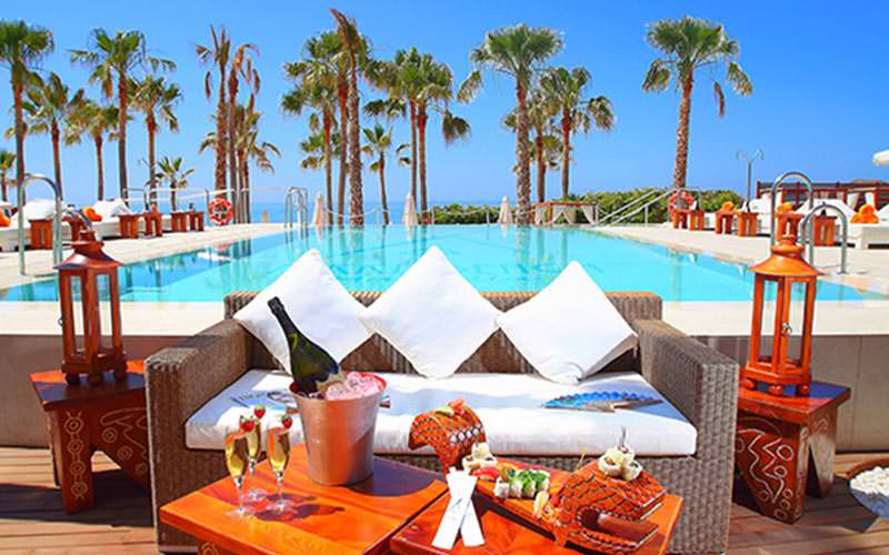 A white sofa behind a table topped with drink and fruit, with the pool and sunbeds in the background