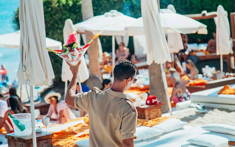 A waiter carrying a bowl of drinks, with people sat on sun beds in the background