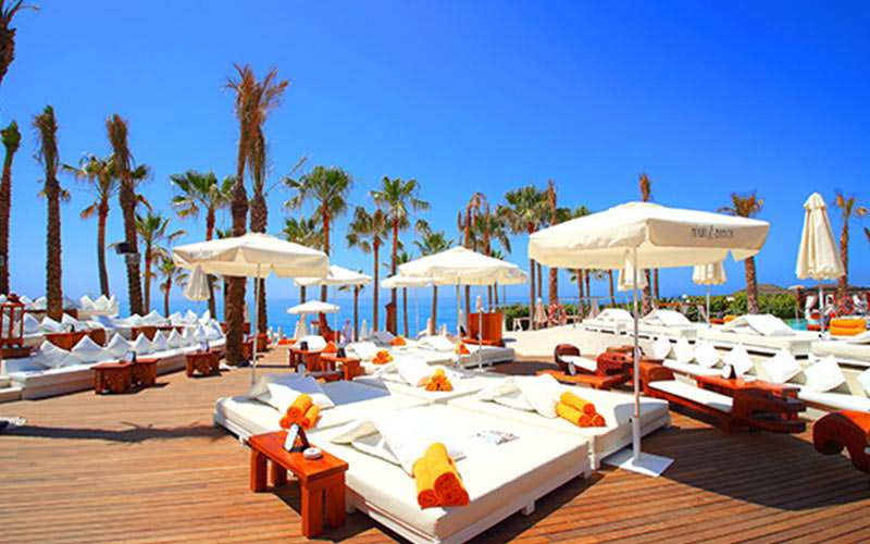 White sun beds topped with towels on the decking at Nikki Beach