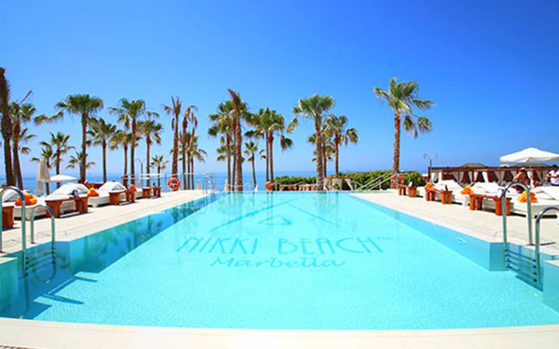 The pool at Nikki Beach with sun beds on either side