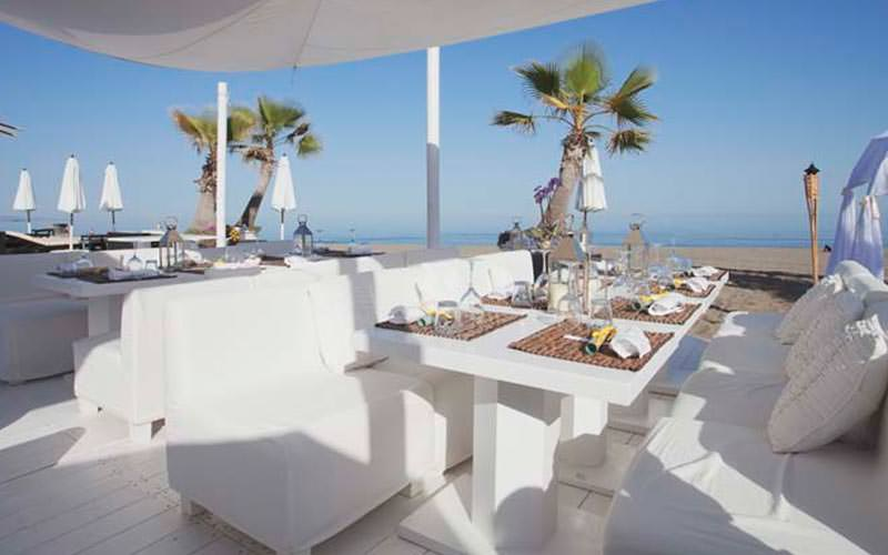 Plush white chairs around a table set for dinner with the beach in the background
