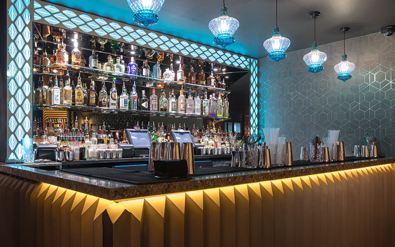 A blue lit bar area in Dirty Martini