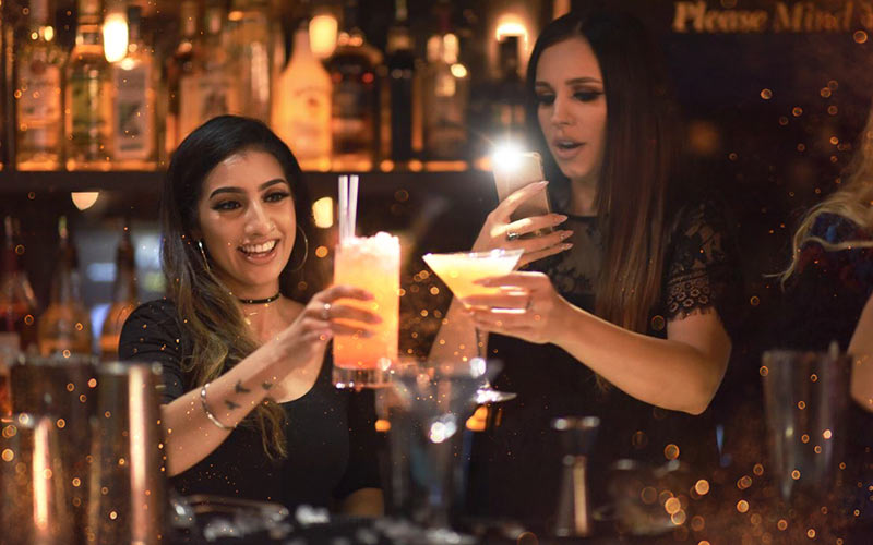 Two girls behind a bar, holding a cocktail each