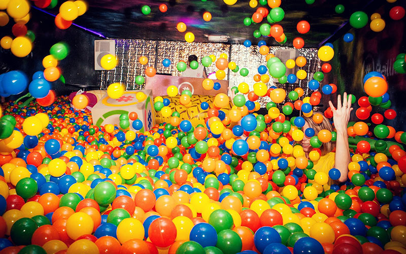 A group of people throwing balls in a ball pit