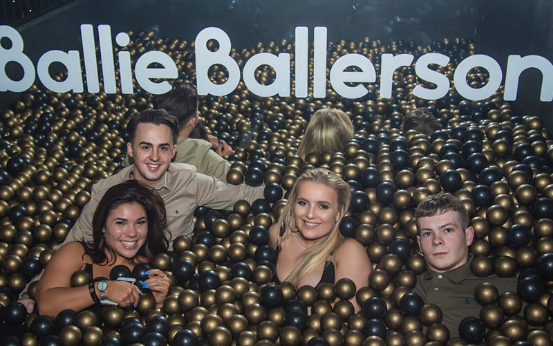 Two men and tow women in a ball pit made up of gold and black balls