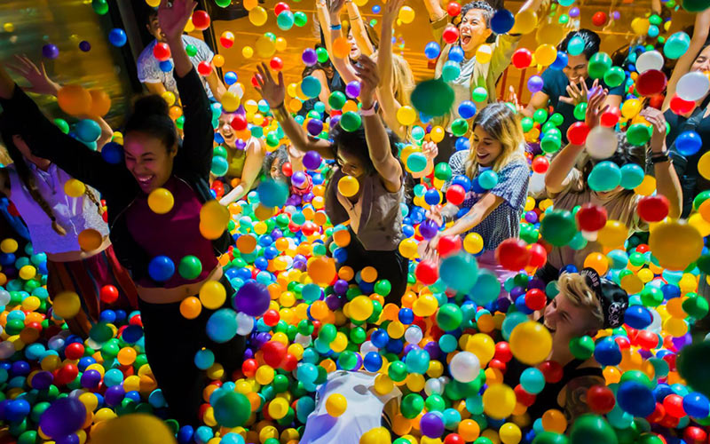 A group of men and women throwing balls in a ball pit