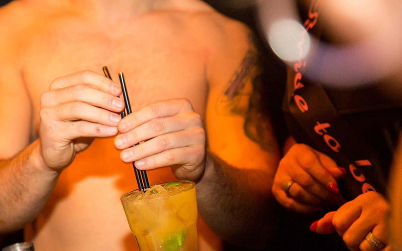 A close up of a topless man holding a yellow drink