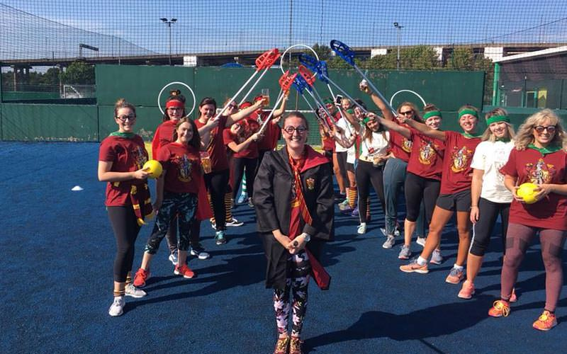 Image of a group of women playing quidditch on a outdoor court wearing harry potter themed outfits