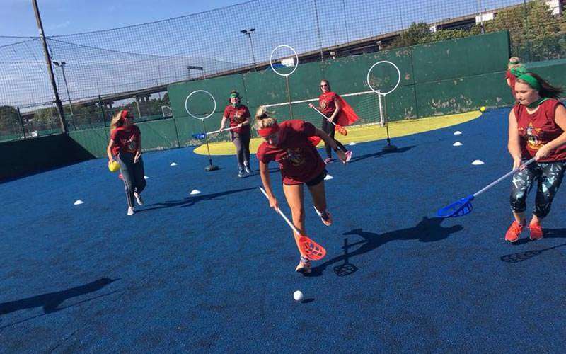 Image of women playing quidditch on a outdoor court