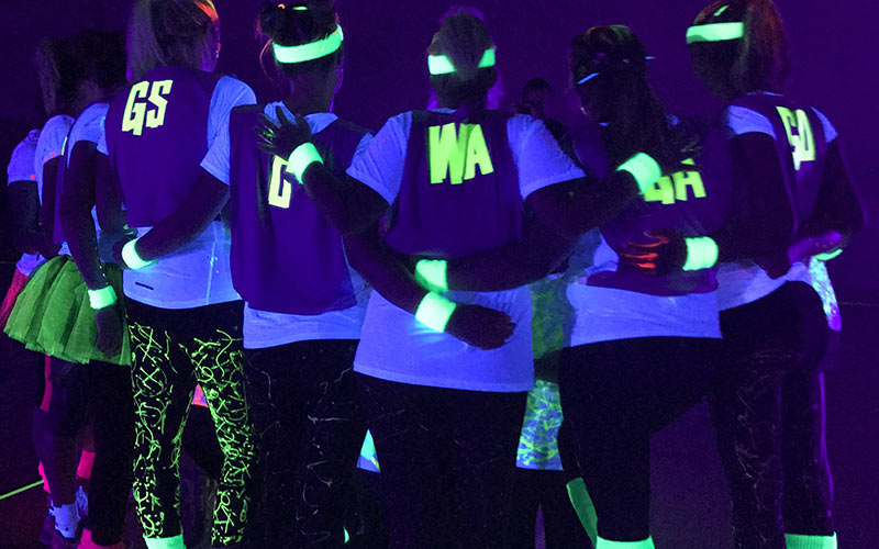 A group of girls huddling in glow in the dark netball vests