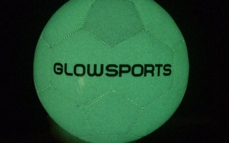 A glow in the dark football with the Glowsports logo on it