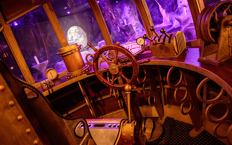 A steering wheel in a dimly lit area of the space golf arena