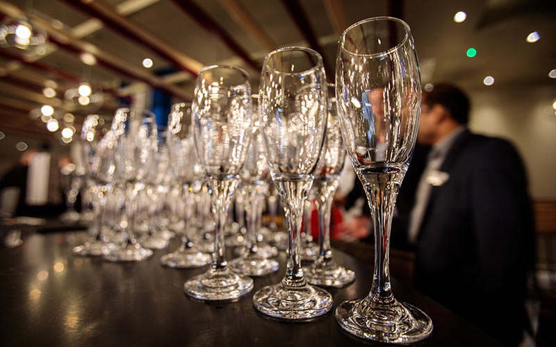 Some Champagne glasses lined up on a bar