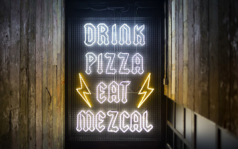 A sign saying 'drink, pizza eat mezcal'