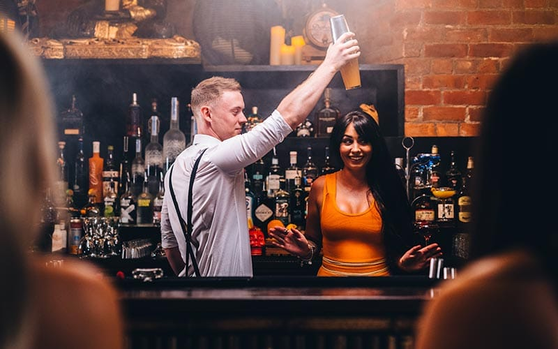 Image of a bartender putting a cocktail shaker onto a womans head