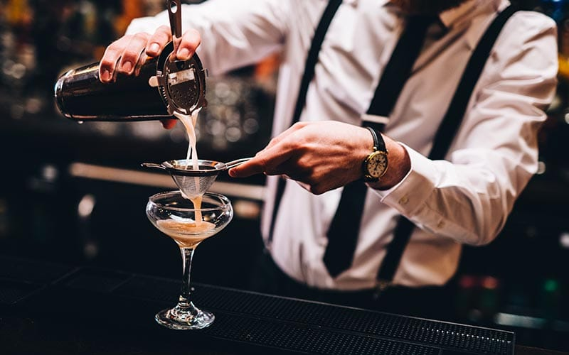Image of a bartender pouring a cocktail through a strainer