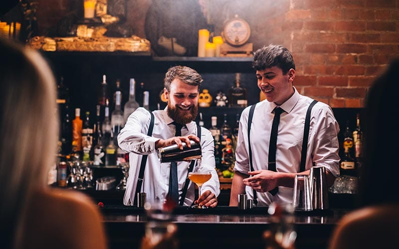 Image of two bartenders pouring cocktails at a bar