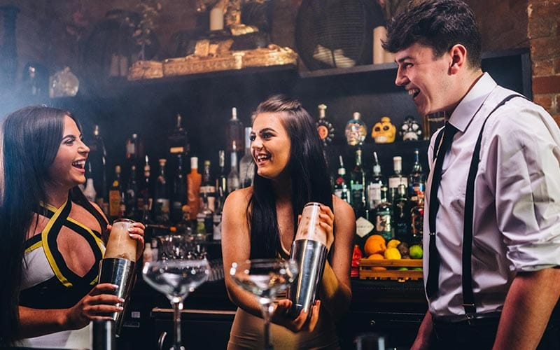 Image of two women laughing and holding cocktail shakers standing beside a bartender