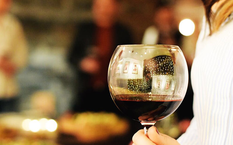 A large glass of red wine in a girls hand, with the restaurant blurred in the background