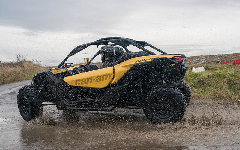 An off road buggy being driven on an outdoor track through the mud