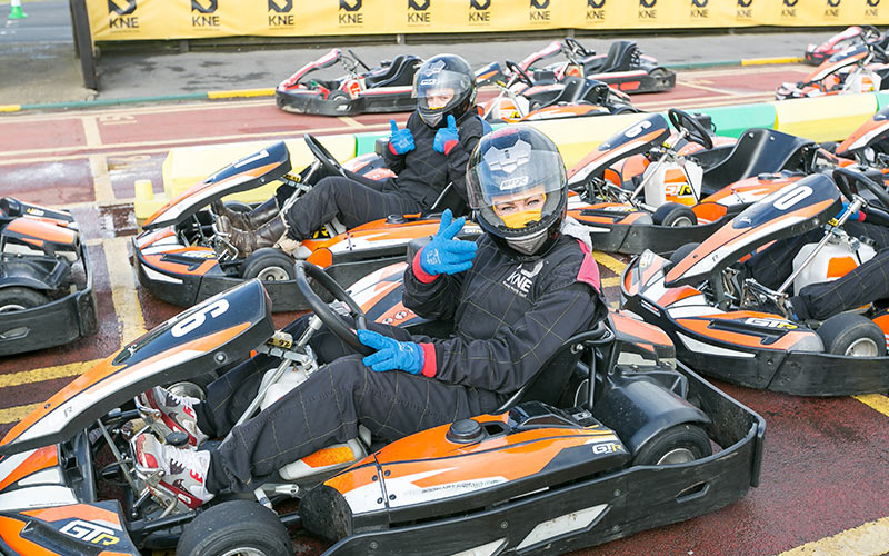 Two people in go karts posing to the camera
