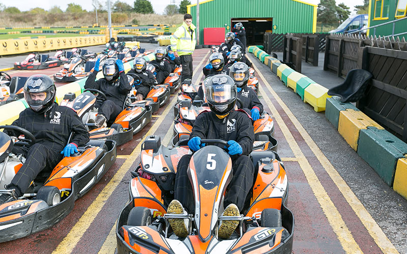 A group of people in go karts outside, ready to race