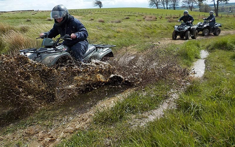 Quad Bike racing through a muddy puddle, spraying the water, with two karts in the background.